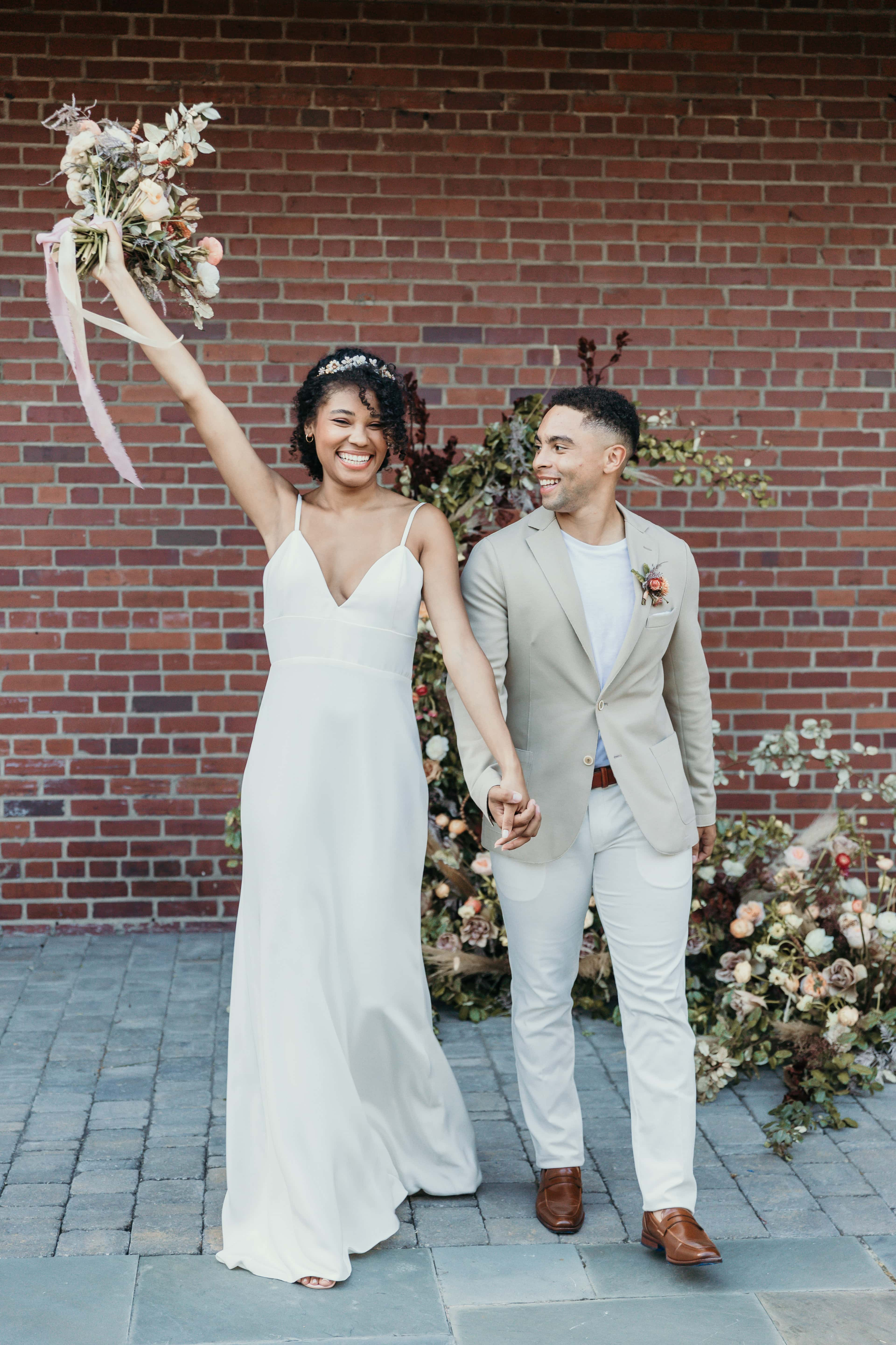 wedding photographer, a delighted bride holds groom's hand, her other hand holds a floral bouquet in the air in celebration
