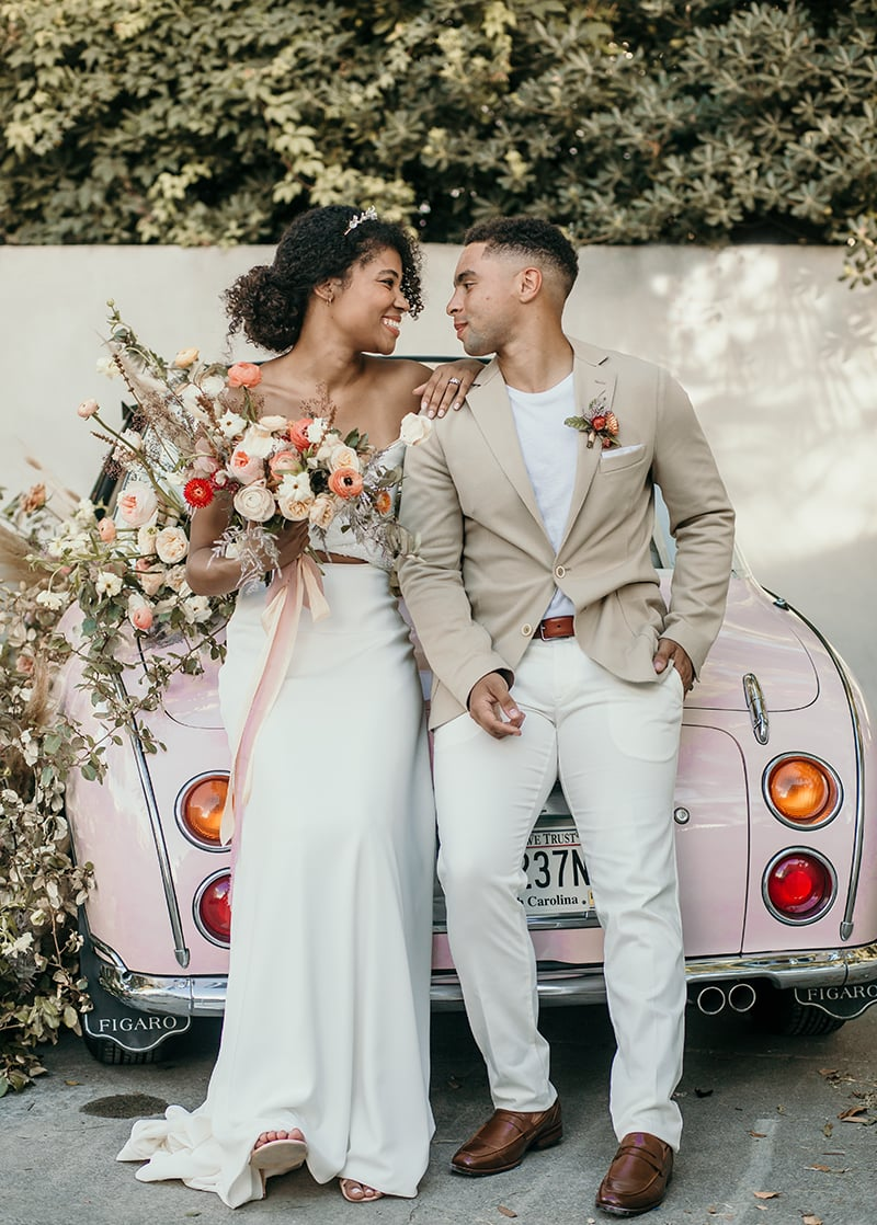 wedding photographer, bride and groom sit on an old car covered in flowers, they smile as they look into each other's eyes