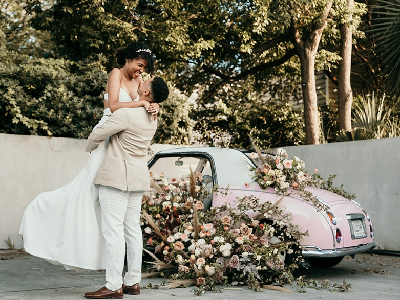 wedding photographer, groom holds his love up in the air, the bride laughs, they stand before an old car covered in flowers