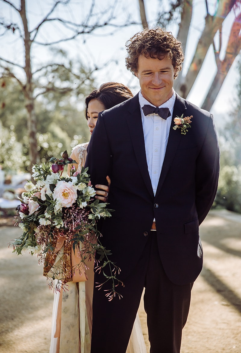 wedding photographer, bride holds her grooms arm from behind as she snuggles in close with her wedding bouquet, he smiles softly