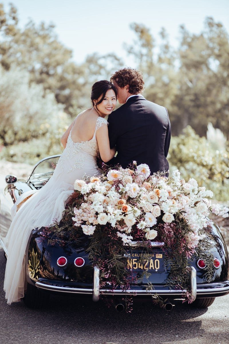 wedding photographer, bride and groom sit on a small car covered in flowers as if to drive away newly weds