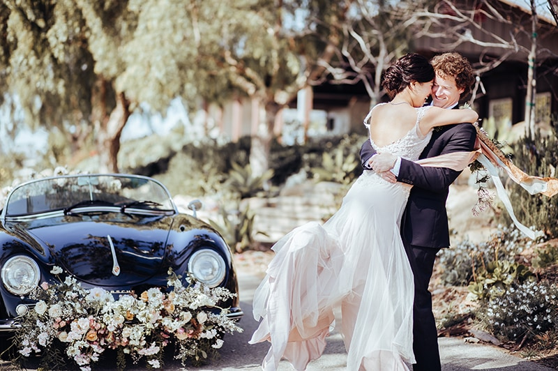 wedding photographer, a groom lifts up his bride outdoors, a car covered in flowers beside them
