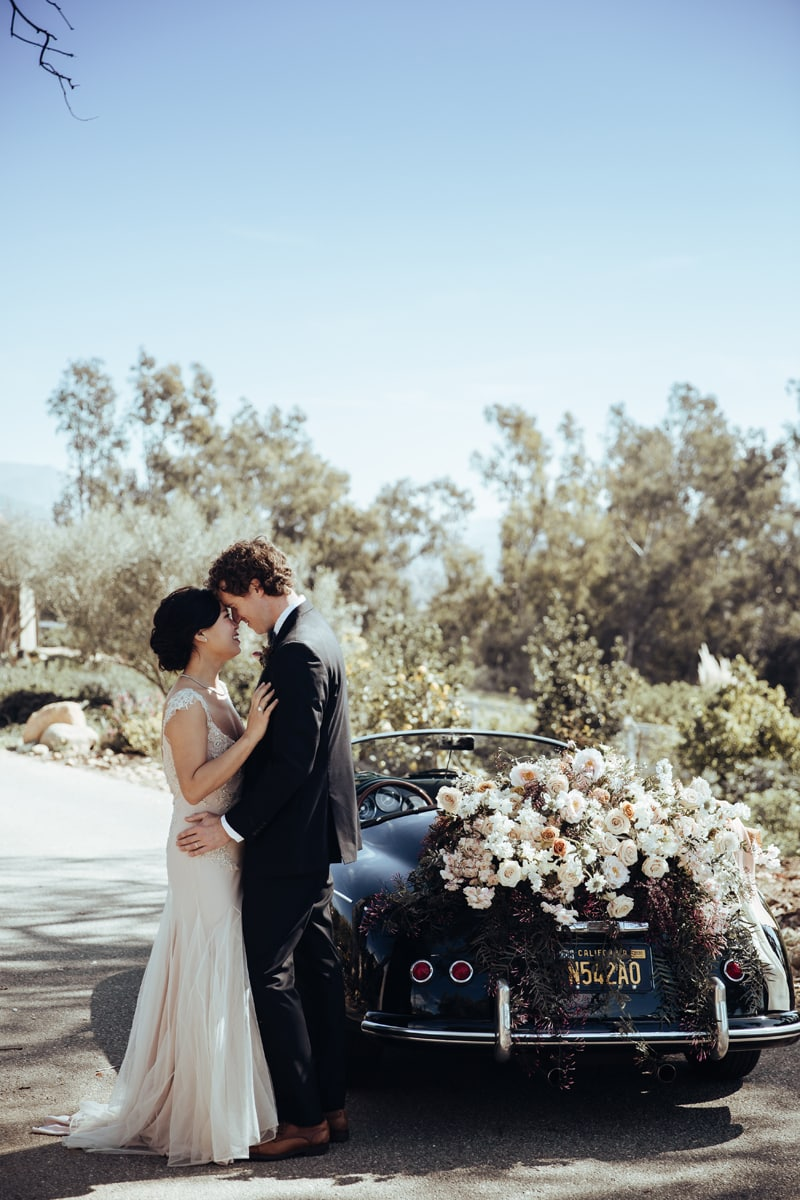 wedding photographer, bride and groom hold each other close outdoors near a car covered in flowers