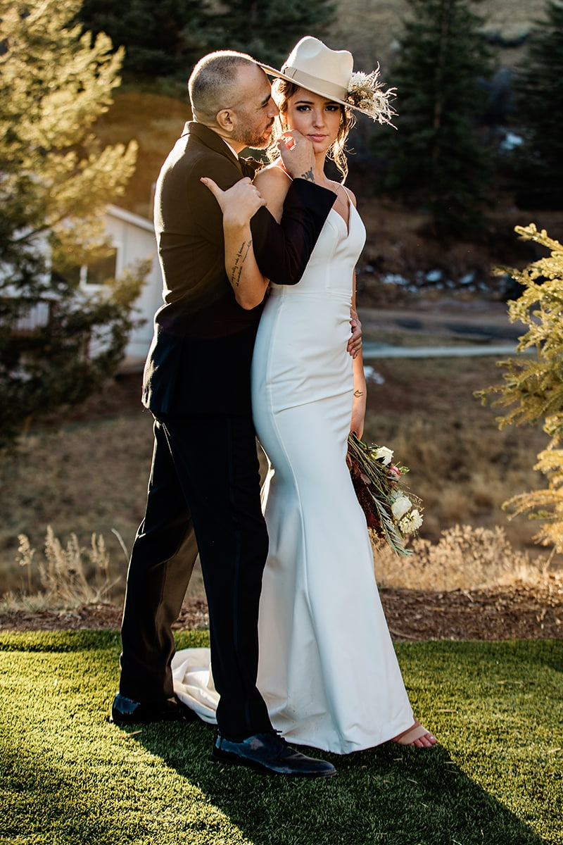 wedding photographer, groom leans in to kiss wife from behind, they are outdoors in the grass