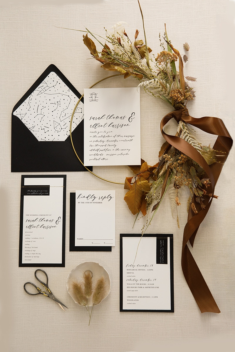 Wedding Photographer, wedding invitations arranged decoratively on the table with scissors and floral arrangement