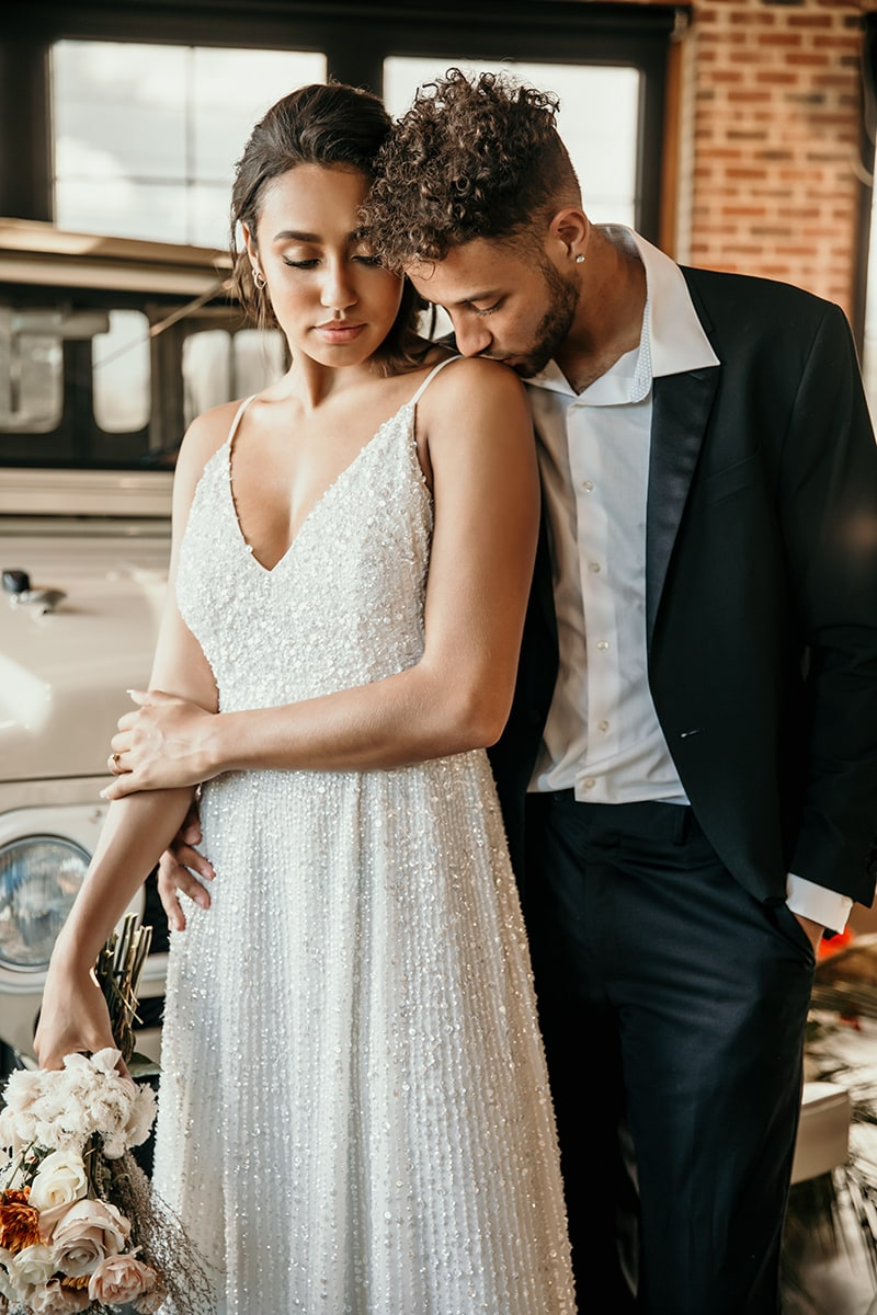 wedding photographer, a groom gently kisses his new bride's shoulder, they stand near an old truck