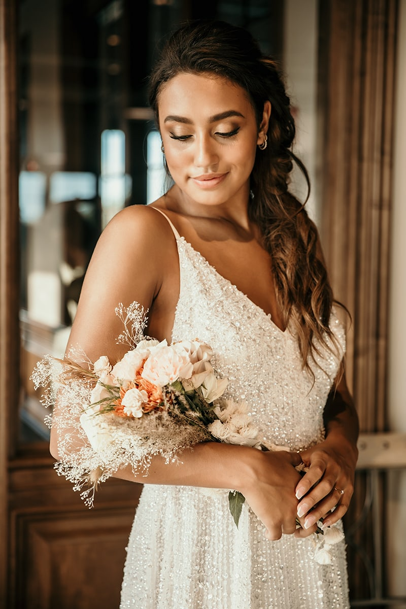 wedding photographer, woman in her wedding dresses grins as she looks down at her wedding bouquet