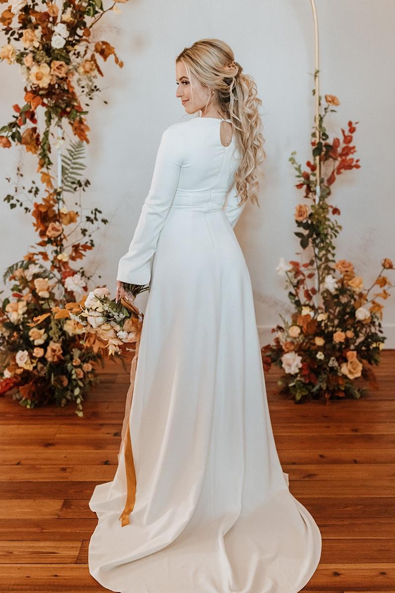 wedding photographer, woman in her wedding dress stands before beautiful floral arrangement indoors