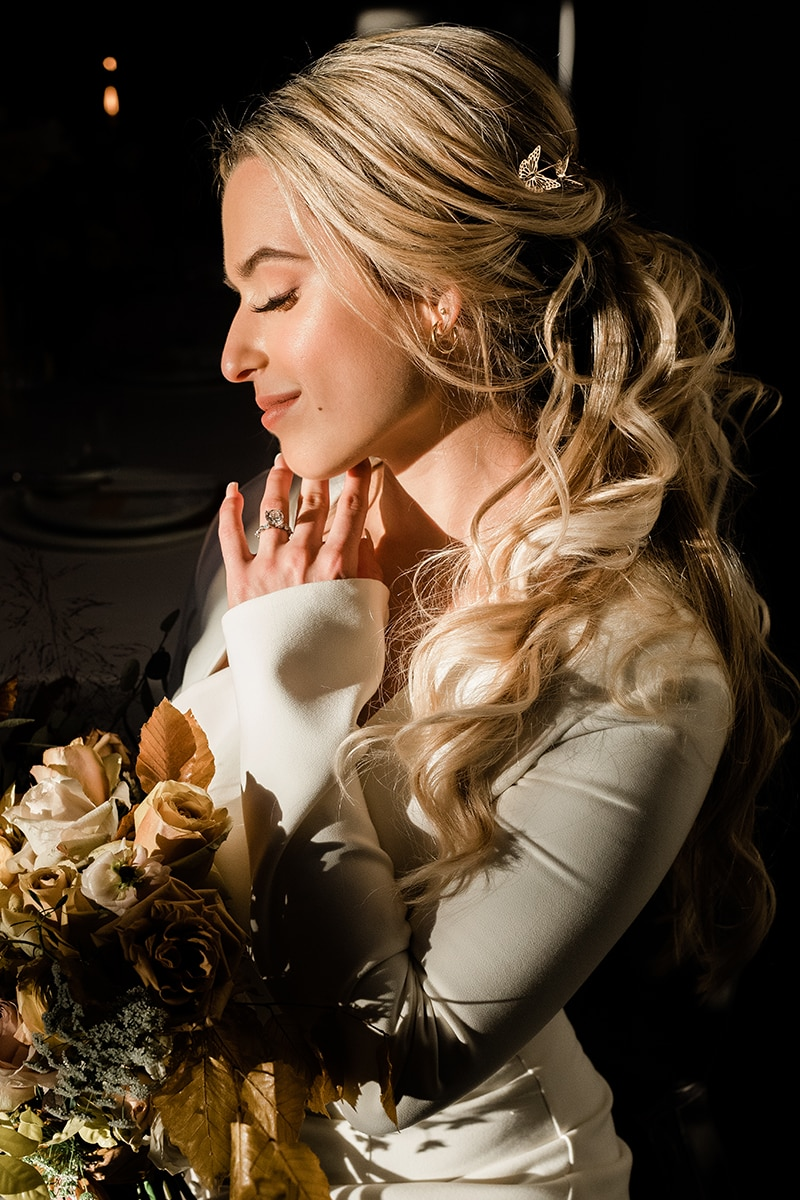 wedding photographer, woman smiles holding her wedding bouquet and has her hand to her face with wedding ring