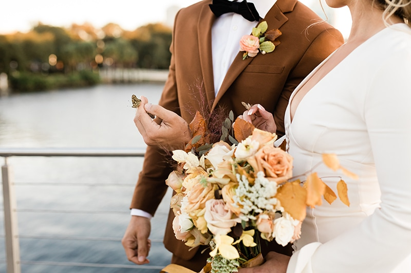 wedding photographer, bride holds bouquet of flowers, a butterfly has landed on groom's hand outdoors before lake