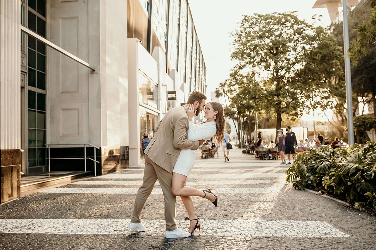 Family and Wedding photographer, Man leans his wife backward as they smile face to face in the city