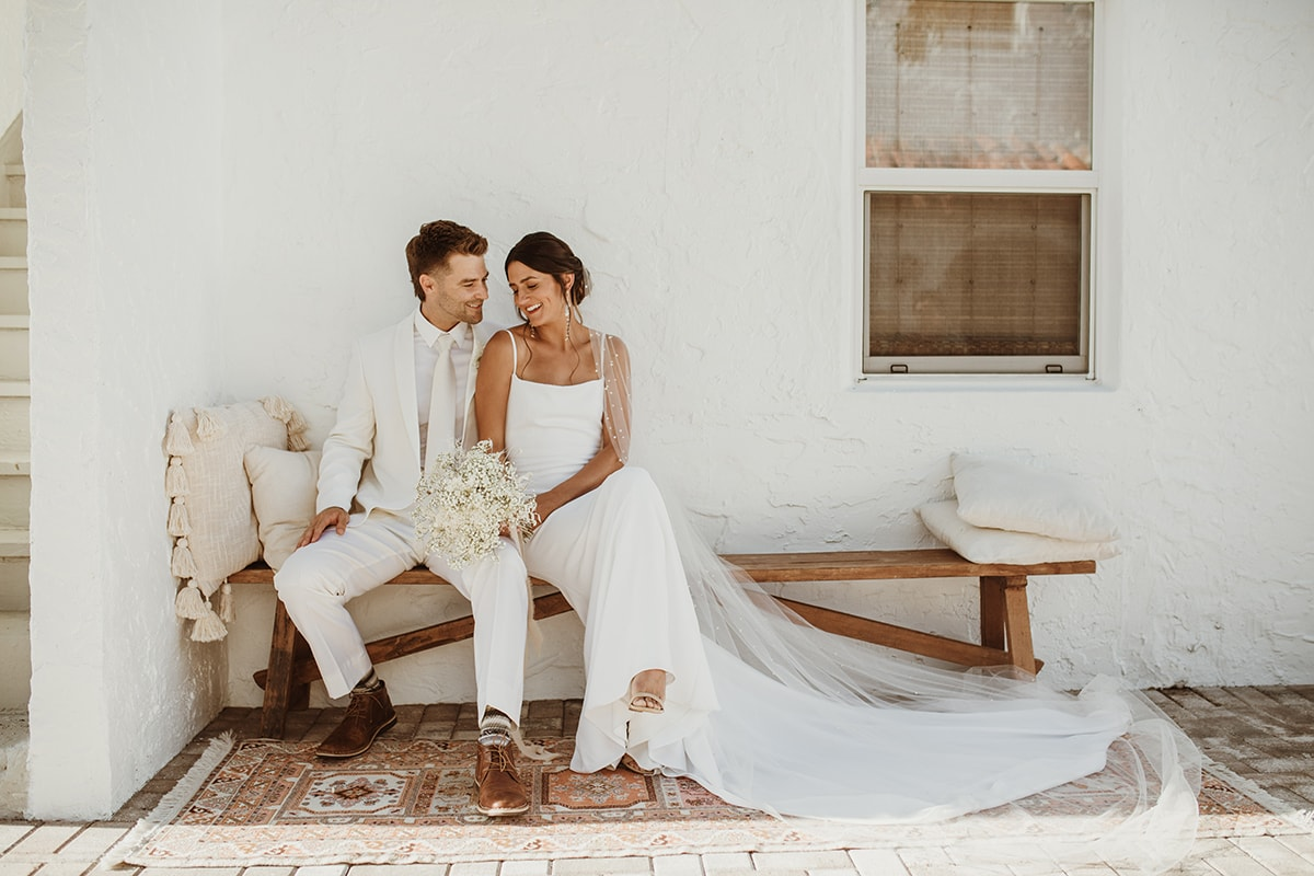 Wedding Photographer, Bride and Groom sit on a wooden bench outside, they both wear white