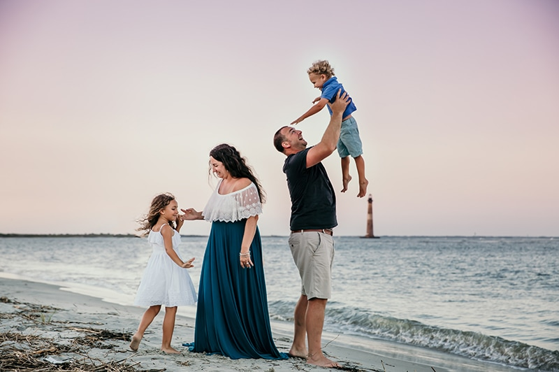 Fort Lauderdale Family Photographer, family of 4 playing at the beach with dad holding up daughter in the air