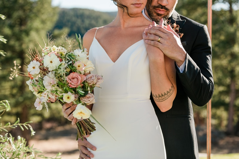 wedding photographer, bride holds her floral bouquet, groom holds her other hand as he embraces her outdoors
