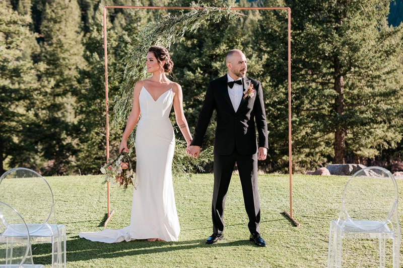 wedding photographer, bride and groom stand in grass before an empty chairs, they are hand in hand