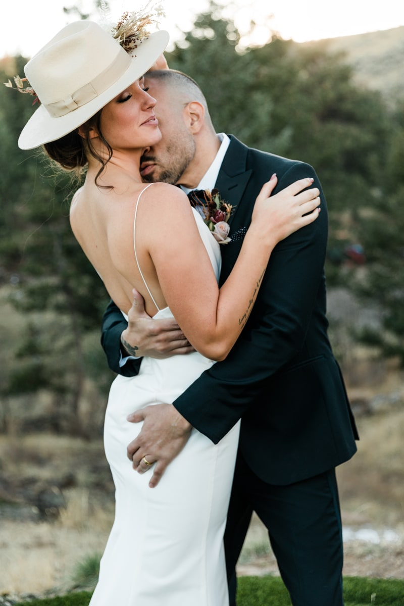 wedding photographer, man in tuxedo leans in to his bride in her wedding dress