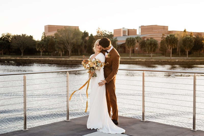 wedding photographer, new bride and groom stand before a lake and gaze into each other's eyes